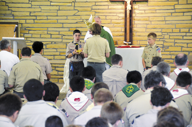 Scout Riley Vandaveer, a member of Prince of Peace Parish in Olathe, Kan., assists Bishop Robert W. Finn as he celebrates Mass July 20 for Catholic Boy Scouts at the H. Roe Bartle Scout Reservation. (Kevin Kelly/Key photo)