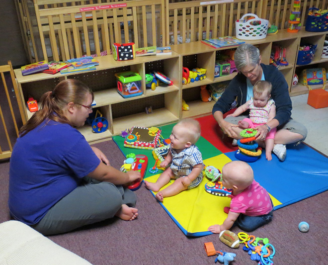 Teachers Helen Walterbach and Mariah Moseley guide infants at the St. Therese Early Education Center through play that is helping their brains grow and develop. (Kevin Kelly/Key photo)