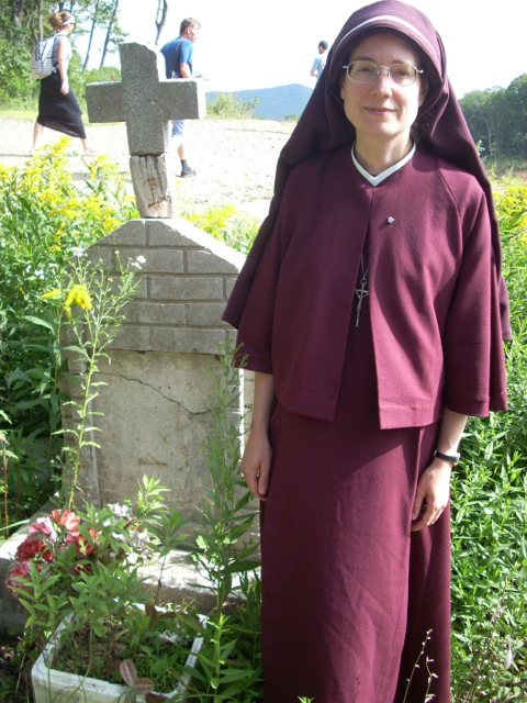 Sister Maria Stella (superior in Russia) stands near the monument for the Catholic Martyrs of the area (including the last five parishioners who were shot while praying the Rosary).