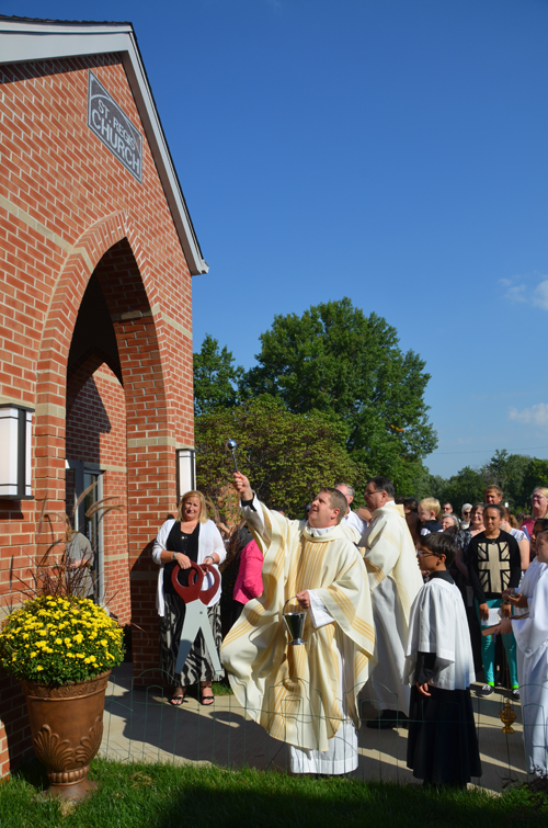 Father Sean McCaffery blesses with holy water the new entrance, with an elevator, Sept. 28 as the people of St. John Francis Regis celebrate the parish's 50th anniversary. (Kevin Kelly/Key photo)
