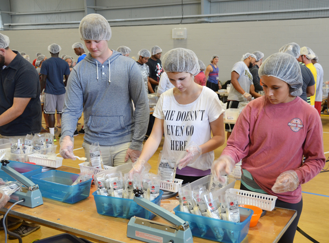 Avila freshmen and Bank of Blue Valley staff members joined forces to help meet the challenge to Stop Hunger Now on Sept. 29. More than 22,000 rice meals were packaged and boxed to be sent to the hungry in developing countries. (Marty Denzer/Key photo)