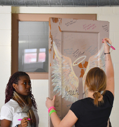 """Not perfect"" team members Avrie Gaupp and Adeline Nkikabahizi write problems they want to break free of on the door following the team's presentation at Our Lady of the Angels School Nov. 17. (Marty Denzer/Key photo)"