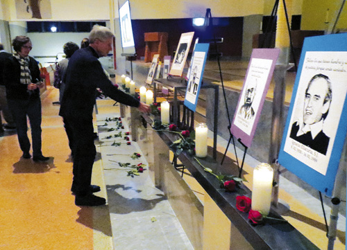 Father Tom Wiederholt lays a rose in front of the images of the six Jesuits murdered 25 years ago in El Salvador during a memorial prayer service November 13 at St. Francis Xavier Parish in Kansas City. (Kevin Kelly/Key photo)