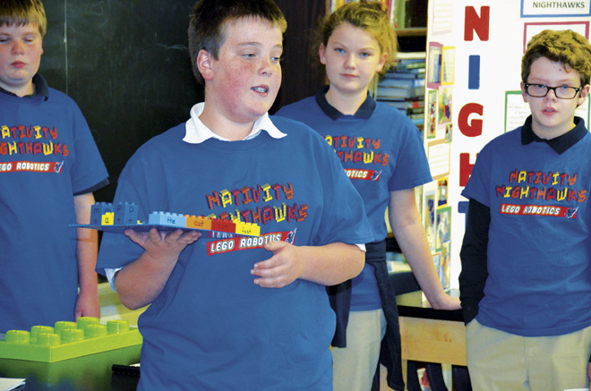 The Nativity of Mary Nighthawks Robotics team explains their math and reading learning aids designed to use with Lego and Duplo building blocks to teachers at a faculty meeting. The blocks are to help students with special needs learn and have fun at the same time. (Marty Denzer/Key photo)