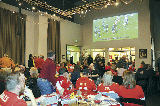 Chiefs fans watch the game against Oakland at the Bright Futures Fund Watch Party at the Roasterie Bean Hanger Nov.20. The event, a benefit for the Strong City Schools, featured food, cheers and groans, and former Chiefs playing auctioneers to raise funds for scholarships. (Marty Denzer/Key photo)