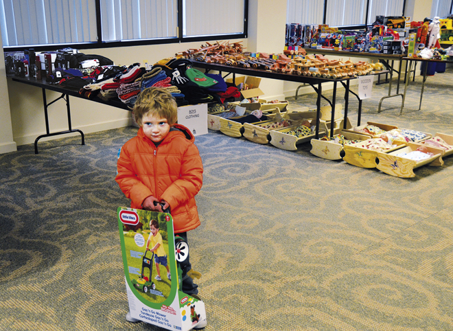 "Unsure whether to smile or cry, Woody clutches the toy lawnmower he picked out for his Christmas present. He was ""shopping"" with his mom at the Christmas Store, part of Project Shining Star, Catholic Charities' annual project to make Christmas happier for families living in poverty. (Marty Denzer/Key photo)"