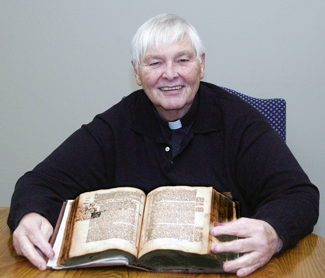 Father John Bolderson shows off the annotations in the margins of one of the three Douay-Rheims Bibles. (Joe Cory/Key photo)