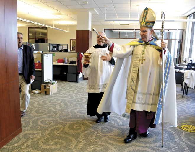 Bishop Robert W. Finn blesses Jan. 7 the headquarters and the employees of Catholic Charities of Kansas City-St. Joseph at the former Merchants' Bank building, 850 Main St. in downtown Kansas City. (Kevin Kelly/Key photo)