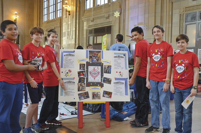 St. Peter's Cosmic Magikarps Robotics team, fifth, sixth and seventh graders Kai and Zayan Barnes,  Seamus Hellings, Leo Gajewski, Matthew Ong and Jack Swanson point out features of their project to redesign education.  (Marty Denzer/Key photo)