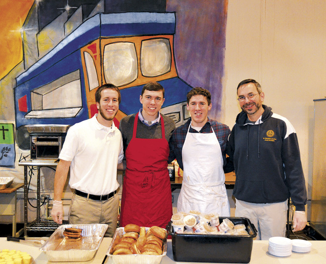 Jesuit novices, Chris McCoy, William Manaker and Matt Hearly served breakfast to guests at the Morning Glory Cafe Jan. 23 with Jesuit Father Mark Thibodeaux, Novice Director for Jesuits in Formation at St. Stanislaus Kostka Novitiate at St. Charles College, Grand Coteau, La. (Marty Denzer/Key photo)