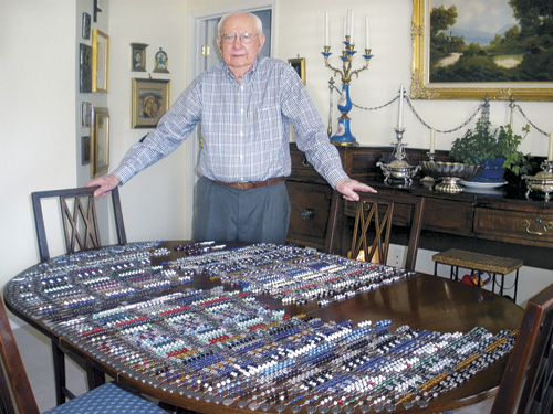 Bob Cunningham displays about 100 of the hundreds of rosaries he has made over the past decade. He makes them from pieces of broken rosaries that people send him or that he picks up at sales. Pieces he doesn't have, he purchases at I. Donnelly Company. Cunningham also makes natural crucifixes from sticks and small rocks.  (Marty Denzer/Key Photo)