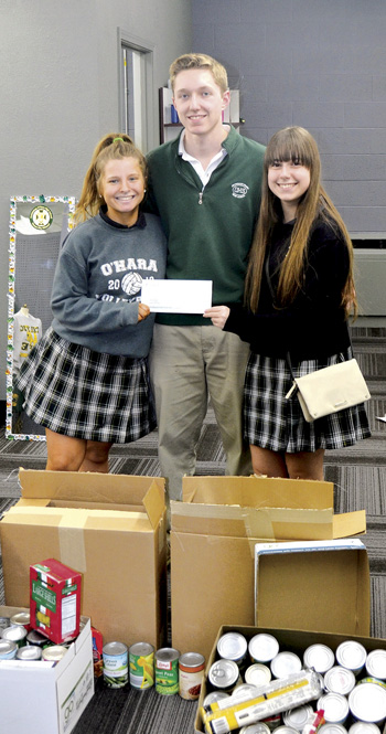 NHS chapter president Nick McCracken shows off the check made out to Catholic Charities with members Rachael Seaver and Laci Haggenga. (Marty Denzer/Key photo)