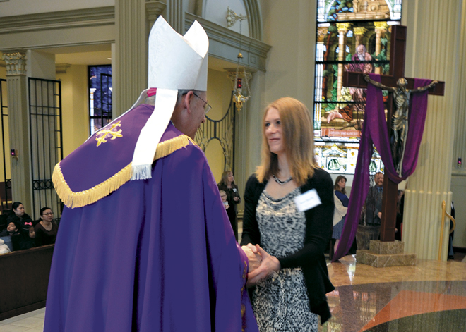 Bishop Robert W. Finn greets Cari Smith at the annual Rite of Election and Call to Continuing Conversion Feb. 21 at the Cathedral of the Immaculate Conception. Smith and her husband Jason will be received into the Catholic Church at Easter Vigil at Twelve Apostles Parish in Platte City. (Kevin Kelly/Key photo)