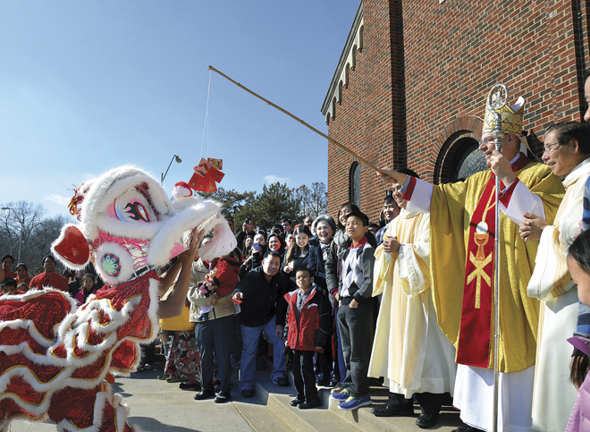 The youth of the Church of the Holy Martyrs brought out a brand new dragon for Bishop Robert W. Finn to feed at the end of the parish's annual Mass Feb. 21 celebrating the Oriental lunar new year of Tet. (Kevin Kelly/Key photo)