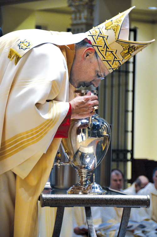 Bishop Robert W. Finn breathes into the Oil of Chrism during the annual Chrism Mass March 26 in which all the oils are consecrated that will be used in sacraments for the next year in the Diocese of Kansas City-St. Joseph. (Kevin Kelly/Key photo)