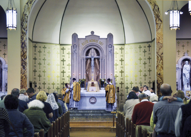 The seated congregation listens as Father Schneider prays aloud in Latin from the sacramentary during the Solemn High Mass on March 17. (Marty Denzer/Key photo)