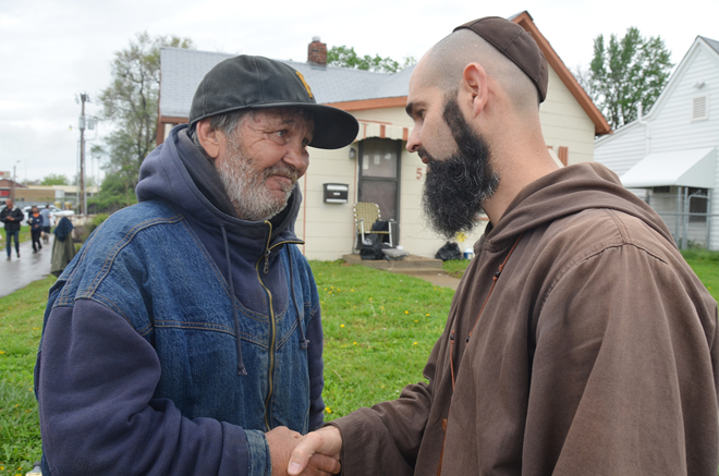 Friar Benjamin greets Larry, a homeless man who was among the poor waiting for a sandwich and a word that somebody cares.  (Kevin Kelly/Key photo)