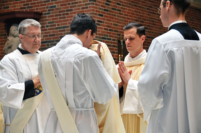 Deacon David Miloscia, who was ordained May 23 to the priesthood of the Archdiocese of St. Louis, vests his brother, newly ordained transitional Deacon Sam Miloscia, who will be ordained to the priesthood of the Diocese of Kansas City-St. Joseph in 2016. (Kevin Kelly/Key photo)