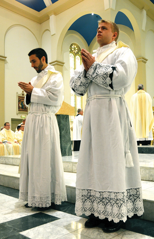 Newly ordained Fathers Andrew Mattingly and Alex Kreidler stand before the altar at the Co-Cathedral of St. Joseph June 27 as they are about to be vested. (Kevin Kelly/Key photo)