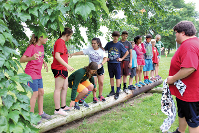 Week 2 campers build team work and balance in this low ropes element experience. (photo courtesy of Vitoria Silva)
