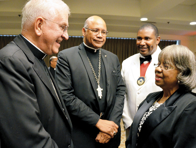 Louisville Archbishop Joseph E. Kurtz and Washington, D.C., Auxiliary Bishop Martin D. Holley speak with Supreme Knight F. DeKarlos Blackmon and Supreme Lady Vertelle Kenion at a reception before the Founders Gala concluding the Knights of Peter Claver annual convention in Kansas City. The banquet raised money for the St. Peter Claver Foundation and its work in advancing educational opportunities for youth. (Kevin Kelly/Key photo)