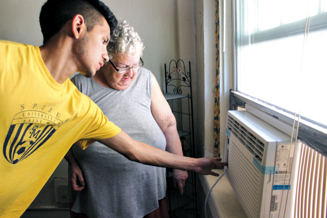 Francisco Sanchez shows a Bishop Sullivan Center client how to set and operate her new air-conditioner, provided free by the center's Project ElderCool program. Sanchez is one of 21 Catholic university students who received summer jobs with social service agencies under a program administered by the Bishop Sullivan Center. (Photo courtesy of the Bishop Sullivan Center)