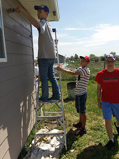 Brenton, Trenton Sill and Patrick Trapp paint a house in Eagle Butte, SD.  (Photo courtesy of Our Lady of Guadalupe Parish.)