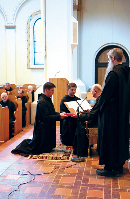 Novice Father Adam Haake receives his copy of the Holy Rule of St. Benedict from Abbot Polan. (photo courtesy of Conception Abbey)