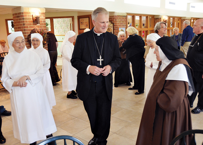 Bishop James V. Johnston greets the Little Sisters of the Poor and Carmelite Sr. Anna Marie Fischer, (right) a resident who had met the Bishop in Springfield when her order was located there. (Joe Cory/Key photo)