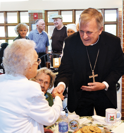 Bishop James V. Johnston greets Wando Oaks, a resident of the Jeanne Jugan Center, on Sept. 15, the day he was named bishop of the Diocese of Kansas City-St. Joseph. (Joe Cory/Key photo)
