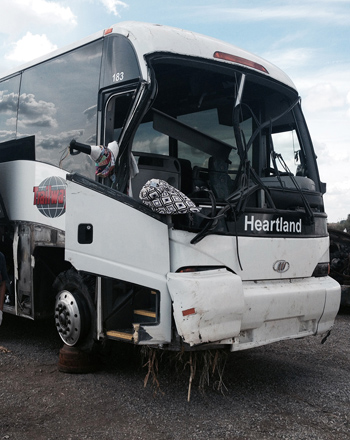 The front of the bus showing the broken windshield and damaged front end and door as well as the blown tire that caused the accident.