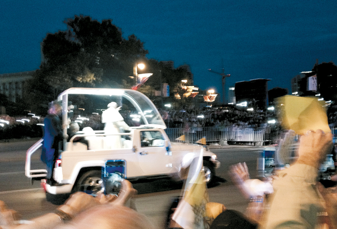 The pope-fiat was moving at a pretty good clip when Kansas City pilgrim Kristen Marquis took this picture of the parade before the start of the Festival of Families the evening of Sept. 25. (Photo courtesy Kristen Marquis)