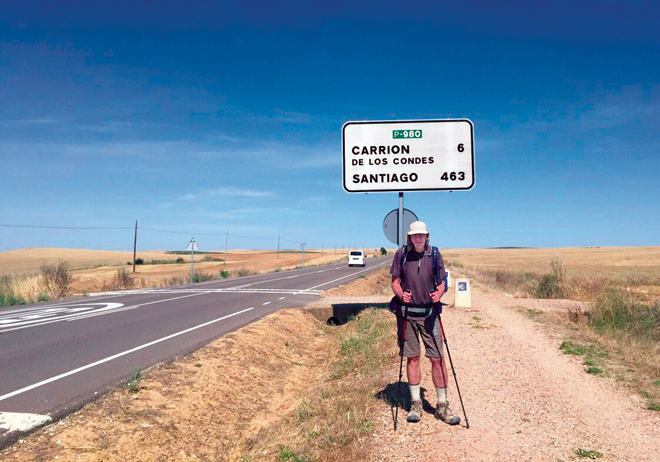 Jesuit Father Tom Curran, president of Rockhurst University, stands near a mileage sign 34 miles into his Camino de Santiago pilgrimage in July 2015. Only 463 miles to Santiago de Campostela. (photo courtesy of Rockhurst University)