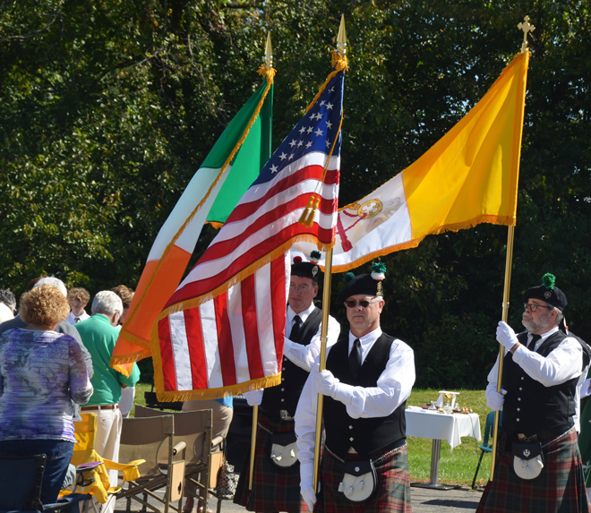 The color guard leads the recessional procession following the Hedgerow Mass. Charlie Lamont carries the Papal flag; Gerard Walsh the Irish flag and Larry Shepard the U.S. flag. (Marty Denzer/Key photo)