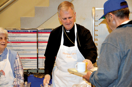 "Bishop Johnston serves orange juice and a warm, friendly ""Good Morning!"" to a breakfast guest at Morning Glory Cafe. (Marty Denzer/Key photo)"