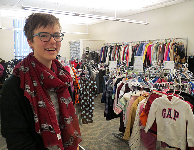 "Catholic Charities intern Katy Kettler, working on a master's degree in social work from Kansas University, assists clients as they choose winter clothes — free — at Catholic Charities of Kansas City-St. Joseph. The ""clothes closet"" is just one of the many services Catholic Charities has been able to provide since its move nearly a year ago into the former bank building at 9th and Main. (Kevin Kelly/Key photo)"