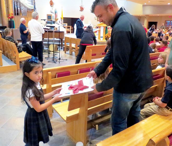 First grader Dominica Falco presented Air Force reservist Rob Thomas with a spiritual bouquet during a Veterans Day Mass at St. John LaLande Parish in Blue Springs. The children at the parish school promised to pray for each of the military veterans attending the Mass, then drew pictures with perfectly handwritten notes telling each of their pledge. (Kevin Kelly/Key photo)