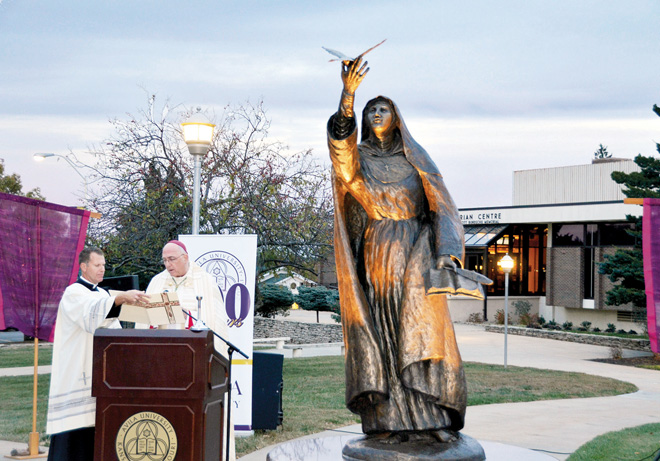 Kansas City, Kan. Archbishop Joseph Naumann, assisted by Father John Riley, archdiocesan chancellor, blesses and dedicates a bronze statue of St. Teresa of Avila, patroness of Avila University, unveiled Oct. 26. (Marty Denzer/Key photo