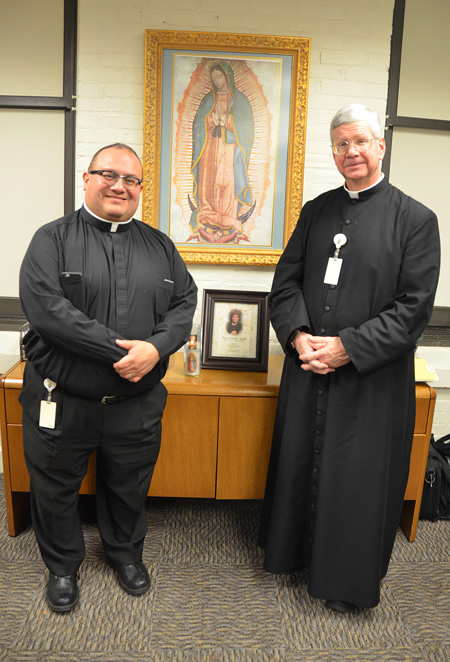"Beneath the icon of Our Lady of Guadalupe, Father Gregory Lockwood and Father Richard Rocha flank a photo of the unofficial ""patron saint"" of the diocesan Vocations Office — Mary Rocha, mother of Father Rocha, who passed away in January. ""She always was a prayer warrior for us. She still is,"" Father Rocha said. (Kevin Kelly/Key photo)"