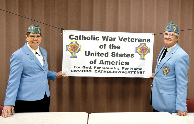Welfare/Service Officer Ann Marie Roberts and Post Commander John Kopp stand before the banner of the Catholic War Veterans now meeting at Our Lady of Mercy Country Home in Liberty. (Marty Denzer/Key photo)