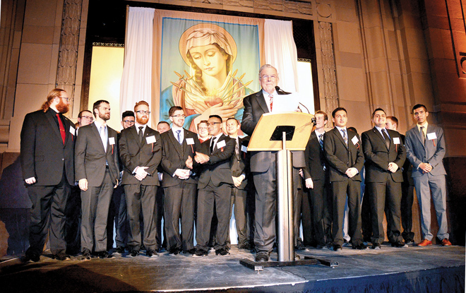 Broadcast legend Larry Moore stands with just some of the seminarians benefitted by the event. This year Conception Seminary College has 108 students and there are 65 seminarians between the Archdiocese of Kansas City in Kansas and the Diocese of Kansas City – St. Joseph. (Jack Smith/Key photo)
