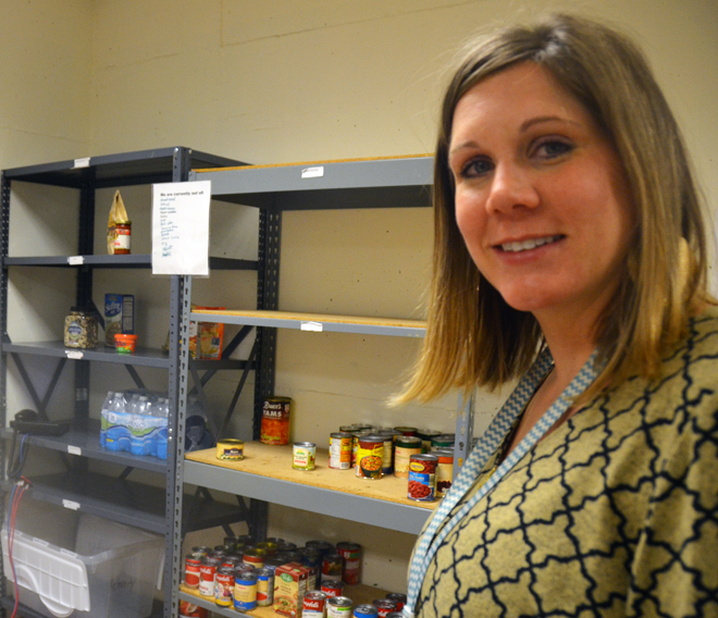 Carrie Pirotte shows the shelves which are getting bare at the emergency food pantry at Catholic Charities downtown Kansas City headquarters. On Feb. 19-20 parishes will be taking up the Catholic Charities Emergency Assistance Fund collection which will not only help restock the pantry, but provide the resources to meet the many needs Catholic Charities of Kansas City-St. Joseph sees throughout the diocese. (Kevin Kelly/Key photo)
