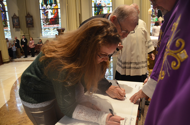 Rachelle Brown, from Holy Rosary Parish in Clinton, and Darrell Moran, from St. Catherine Mission in Osceola, sign the Book of the Elect during the Rite of Election and Call to Continuing Conversion Feb. 13 at the Cathedral of the Immaculate Conception. They will be baptized, confirmed and receive Holy Eucharist at the Easter Vigils in their home communities. (Kevin Kelly/Key photo)