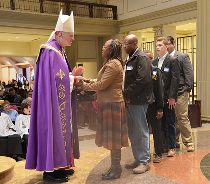 Bishop James V. Johnston Jr. greets candidate Beatrice Wachiea from St. Andrew Parish in Gladstone during the Rite of Election Feb. 13 at the Cathedral of the Immaculate Conception. (Kevin Kelly/Key photo)