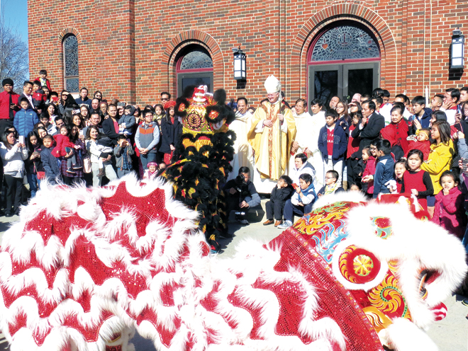 Youth from the Fun Lans (Fun Lions) Club at the Church of the Holy Martyrs perform a ceremonial and acrobatic dance in which the hungry dragons, an Oriental symbol of power and good, vanquish the snake, a symbol of evil, as Bishop James V. Johnston Jr. and the congregation watch. The dance was performed at the end of the annual Mass celebrating the Oriental new year. (Kevin Kelly/Key photo)