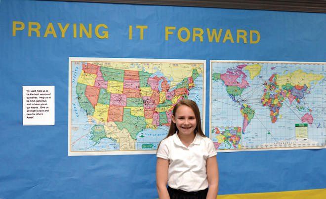 Mikayla Stegner, author of a prayer gone 'round the world, stands by maps tracking where her prayer is being said. She is excited at the thought that it might even reach Pope Francis. (Marty Denzer/Key photo)