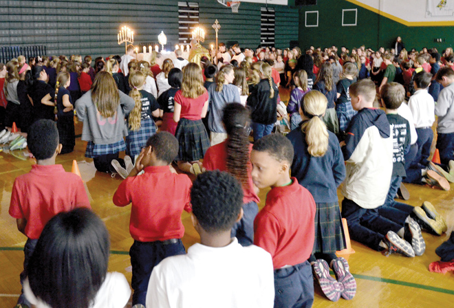 Hundreds of students kneel on the Archbishop O'Hara High School gym floor in absolute reverence Feb. 25 as Father Gabriel Lickteig brings the Blessed Sacrament for adoration at the close of Fifth Grade Vocation Days. (Kevin Kelly/Key photo)