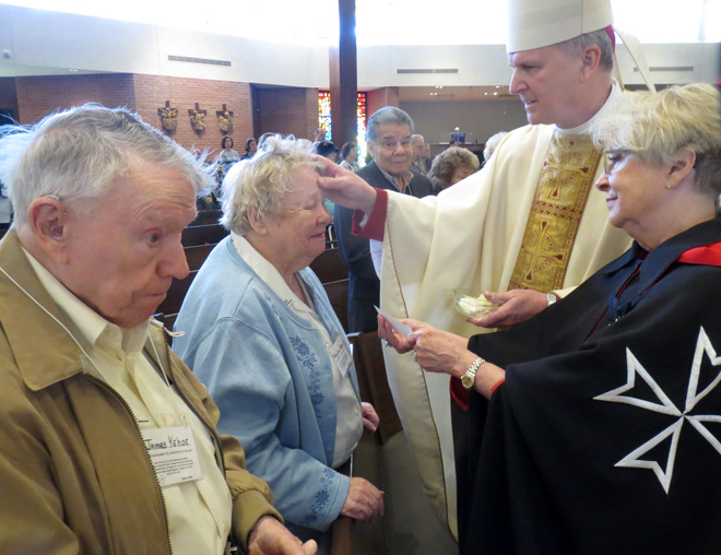 Bishop James V. Johnston, assisted by Georgia Lynch of the Order of Malta, anoints Mary Lou and James Kehoe at the 20th annual Mass for the Anointing of the Sick March 4 at Cure of Ars Parish in Leawood, Kan. (Kevin Kelly/Key photo)