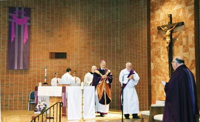Father Joseph Sharbel, pastor, waits at the sanctuary's edge as Bishop James Johnston approaches his chair before the First Reading, during St. Gabriel Archangel's 60th Anniversary Mass March 6. (Marty Denzer/Key photo)