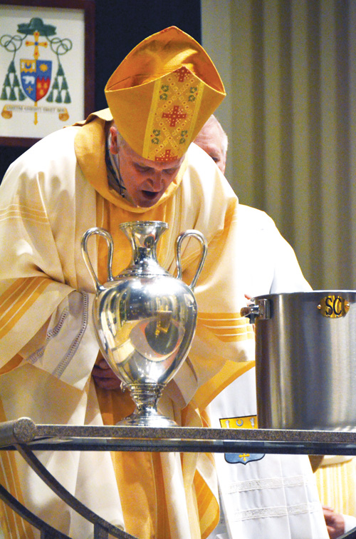 Bishop James V. Johnston Jr. breaths into the Oil of Chrism, symbolic of the life-giving breath of God, at the Chrism Mass March 16 at the Cathedral of the Immaculate Conception. (Kevin Kelly/Key photo)